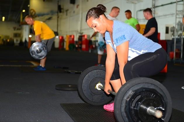 Mulher faz levantamento de peso na academia